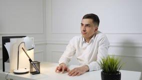 Förhalar den unga mannen för kontorsanställd sammanträde på arbete på kontorstabellen arkivfilmer