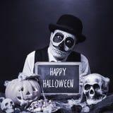 Förklädd man med den svart tavlan med text lyckliga halloween, b&w Arkivbild