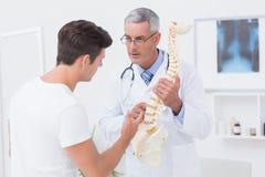 Förklarande anatomisk rygg för doktor till hans patient arkivbild