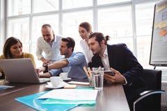 Förklarande kollegor för affärsman med bärbara datorn i mötesrum Fotografering för Bildbyråer