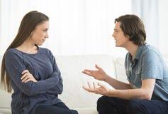 Förklarande kvinna för man, medan argumentera i vardagsrum fotografering för bildbyråer