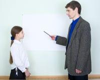 förklarar schoolgirlen något lärare till Arkivbild