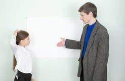 förklarar schoolgirlen något lärare till Royaltyfria Bilder