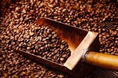 Förkoppra skeden i kaffebönor Arkivfoto