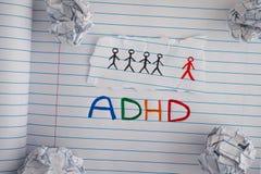 Förkortning ADHD på anteckningsbokarket med någon skrynklig pappersbal fotografering för bildbyråer