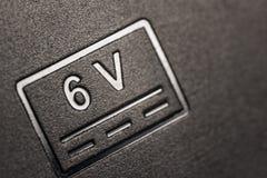 Förkortning 6 volt på kroppen arkivbilder