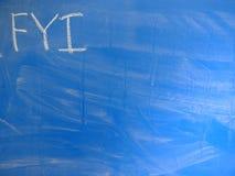 FörkortningsFYI-For Your Information vanligt som är skriftligt på en blått, förhållandevis smutsig svart tavla vid krita Lokalise royaltyfria bilder