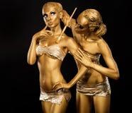 Förkroppsliga konst. Kvinnamålning förkroppsligar med målar borstar i guld- färgar. Guld- smink arkivfoto