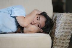 Förkrossad ung härlig för soffasoffa för ledsen och deprimerad asiatisk japansk kvinna hemmastadd känsla lida ångestkris och royaltyfria bilder