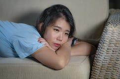 Förkrossad ung härlig för soffasoffa för ledsen och deprimerad asiatisk japansk kvinna hemmastadd känsla lida ångestkris och royaltyfri bild
