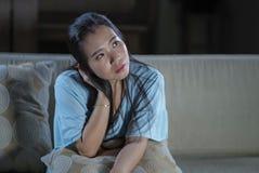 Förkrossad ung härlig för soffasoffa för ledsen och deprimerad asiatisk koreansk kvinna hemmastadd känsla lida ångestkris och royaltyfria foton