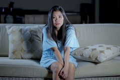 Förkrossad ung härlig för soffasoffa för ledsen och deprimerad asiatisk koreansk kvinna hemmastadd känsla lida ångestkris och arkivfoto