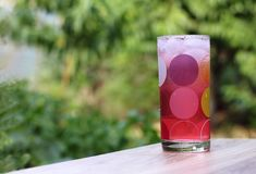 Förkylning rosa fruktsaft med is i en glass kopp för droppe på ett trä i den gröna trädgårds- bakgrunden arkivfoton