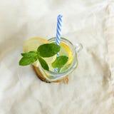 Förkylning, uppfriskande drink med citronen och blad av mintkaramellen i exponeringsglas på tabellen Royaltyfri Foto