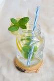 Förkylning, uppfriskande drink med citronen och mintkaramell i exponeringsglas på tabellen Royaltyfri Fotografi