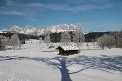 Förlägga i barack med reflexion av trädet i snö, Kitzbuhel Royaltyfri Fotografi