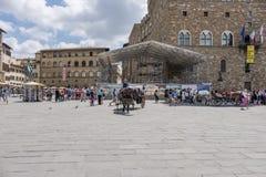 Förlägga kallade de la Signoria med en typisk hästbarnvagn och många turister som strosar på en solig dag, på den rätten arkivbild