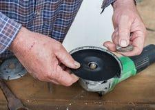 Förlägga sandpappra skivahållaren på fästandebulten av vinkelmolar Fotografering för Bildbyråer