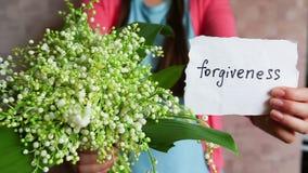 Förlåtelse - härlig kvinna med buketten av vita blommor och ordet på kort stock video