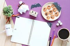 Förlöjliga upp av den öppna anteckningsboken, pappers- hantverk, kubkalender, grillade morötter med den läskiga framsidan och kaf Arkivbilder