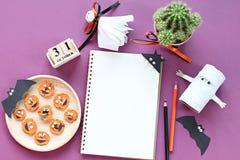 Förlöjliga upp av den öppna anteckningsboken, pappers- hantverk, kubkalender, grillade morötter med den läskiga framsidan och kaf Fotografering för Bildbyråer