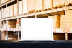 Förlöjliga upp av den moderna datoren eller bärbara datorn med den tomma skärmen på tabellen med suddiga askar på rader av hyllor arkivfoto