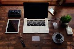 Förlöjliga upp av det frilans- skrivbordet med tillbehör och avståndsarbetshjälpmedel, bärbar datordatoren för tom skärm och den  Royaltyfria Foton