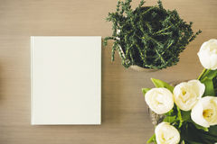 Förlöjliga upp bokomslag på tabellen med den vita blomman för växten royaltyfria bilder