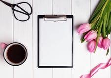 Förlöjliga upp med tomt papper, rosa tulpan och kaffe på viten wo fotografering för bildbyråer