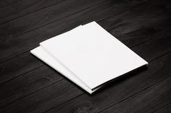 Förlöjligar den tomma broschyren för företags identitet två på svart stilfull wood bakgrund, upp arkivfoton