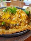 F?rlade ostron blandade med ?gg och frasig deggarnering med koriander i en varm panna och royaltyfri foto