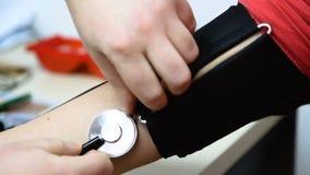 Förlade remmar av mäta apparater för blodtryck på den kvinnliga handen stock video