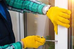 Förlage med skruvmejseln som reparerar ett fönster Royaltyfri Fotografi