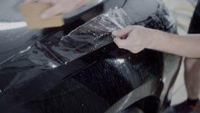 Förlagen applicerar ett skyddande lager på yttersidan av bilen lager videofilmer