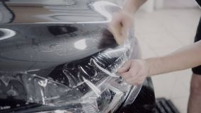 Förlagen applicerar ett skyddande lager på yttersidan av bilen stock video