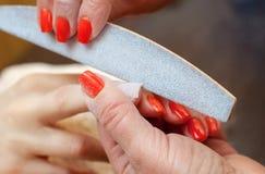 Förlagen av manikyren sågar och fäster en spikaform under tillvägagångssättet av spikar förlängningar med stelnar i skönhetsalong Royaltyfri Fotografi