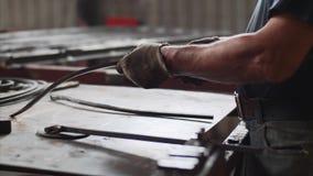 Förlagen böjer metallstången i last på arbetsplatsen för tillverkning av metallstrukturer arkivfilmer