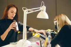 Förlagen gör en manikyr Avslappnande dag på skönhetsalongen Manikyristförlagen gör manikyr på handen för kvinna` s Flickamålarfär royaltyfria bilder