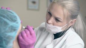 Förlagen i maskering gör krön som tatuerar på kvinnaframsida i klinik stock video