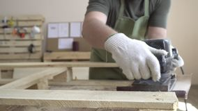 Förlagen i vita handskar och ett grönt förkläde arbetar med hjälpmedel för att mala På bakgrunden av brädet med anvisningar arkivfilmer