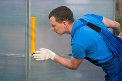 Förlagen kontrollerar riktigheten av montering av växthuset som göras av polycarbonaten arkivfoton
