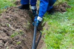 Förlagen lägger ett rör i jordningen för en sommarvattenförsörjning i ett landshus fotografering för bildbyråer