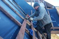 Förlagen stoppar till spikar in i en stråle som fixar denna gidrorizer till taksparrarna arkivbilder