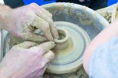 Förlagen undervisar barnet, en student av krukmakeri Hjälp som ska göras ut ur lera på en keramiker` s, rullar en tillbringare Royaltyfri Bild
