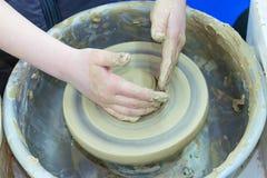 Förlagen undervisar barnet, en student av krukmakeri Hjälp som ska göras ut ur lera på en keramiker` s, rullar en tillbringare arkivfoto