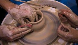 Förlagen undervisar studenten konsten av krukmakeri royaltyfria foton