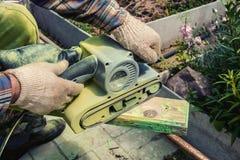 Förlagen vässar den wood panelen med en elektrisk slipmaskin för en solig dag Arkivfoto