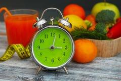 förlora tid att weight Frukt, grönsaken och och exponeringsglas av fruktsaftringklockan på tabellen, bantar och konditionbegreppe Royaltyfria Bilder