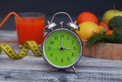 förlora tid att weight Frukt, grönsaken och och exponeringsglas av fruktsaftringklockan på tabellen, bantar och konditionbegreppe Royaltyfri Bild