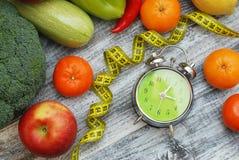 förlora tid att weight Frukt, grönsaken och ringklockan på tabellen, bantar och konditionbegreppet Lekmanna- lägenhet Royaltyfria Bilder